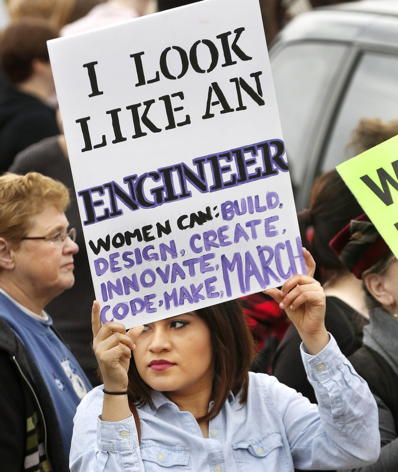 Photo - A woman holds a large sign as she joins others in the march on Lincoln Blvd. A crowd estimated by organizers to be as many as 7,000 people came to the state Capitol in Oklahoma City Saturday, Jan. 21, 2017, to rally, using their voices and signs to express displeasure with the nation's new administration as part of a larger network of marches taking place across the country following Donald Trump's inauguration.   The Women's March on Oklahoma included a walk along Lincoln Blvd., with the Capitol as a backdrop, and a rally on the Capitol's south plaza that featured nearly a dozen speakers.  Photo by Jim Beckel, The Oklahoman