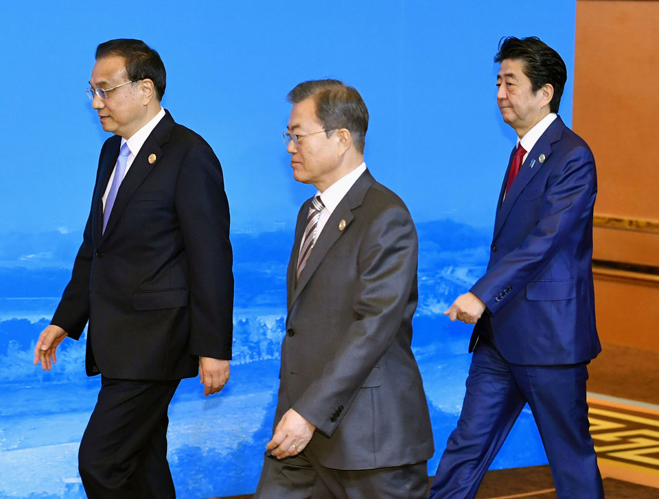 Photo -  Chinese Premier Li Keqiang, left, South Korean President Moon Jae-in, center, and Japan's Prime Minister Shinzo Abe, right, walk to a group photo session before the trilateral meeting between China, South Korea and Japan in Chengdu, southwest China's Sichuan province Tuesday, Dec. 24, 2019. (Yoshitaka Sugawara/Kyodo News via AP)