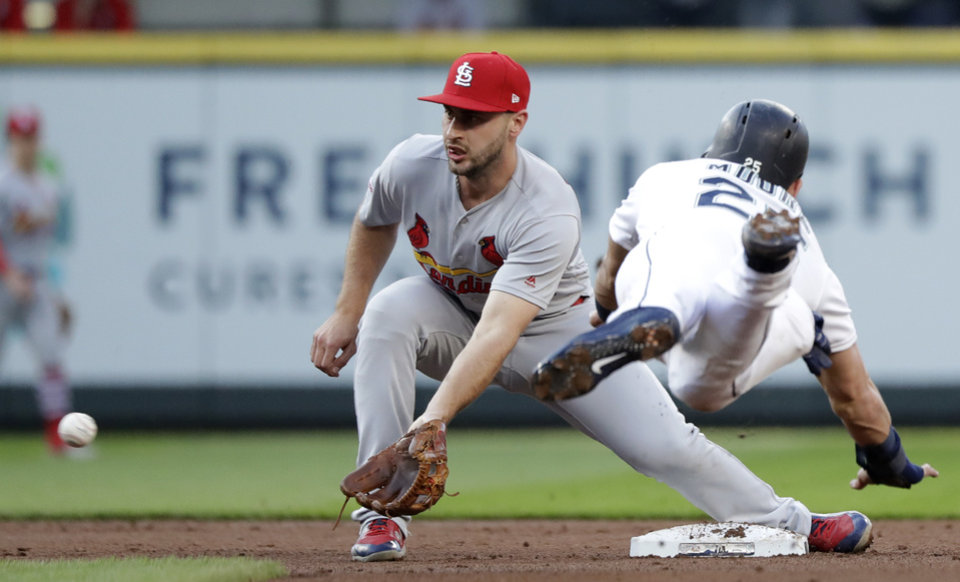 Photo -  Cardinals shortstop Paul DeJong, left, reaches for the ball before tagging out the Mariners' Dylan Moore at second on a stolen-base attempt during the second inning July 3 in Seattle. [Elaine Thompson/the associated press]