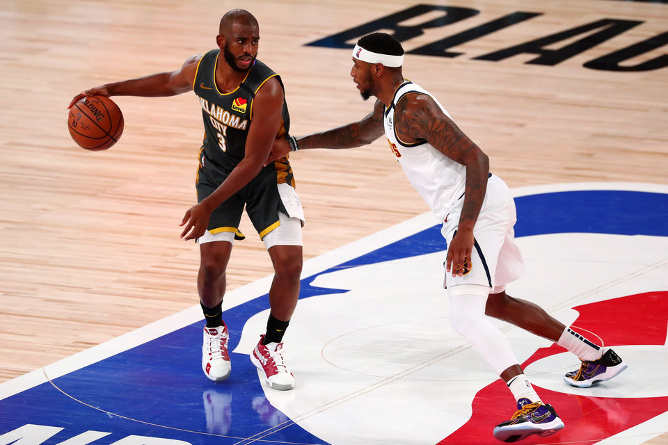 Photo - Aug 3, 2020; Lake Buena Vista, Florida, USA; Oklahoma City Thunder guard Chris Paul (3) handles the ball against Denver Nuggets forward Torrey Craig (3) during the third quarter in a NBA basketball game at The Arena. Mandatory Credit: Kim Klement-USA TODAY Sports