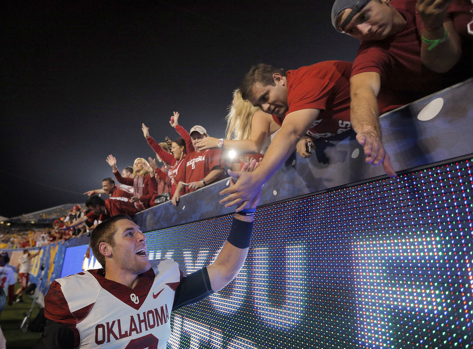 Photo - Oklahoma's Trevor Knight (9) celebrates with fans following the college football game between West Virginia  Mountaineers and the University of Oklahoma Sooners at Milan Puskar Stadium in Morgantown, W.Va., Saturday, Sept. 20, 2014. Photo by Sarah Phipps, The Oklahoman