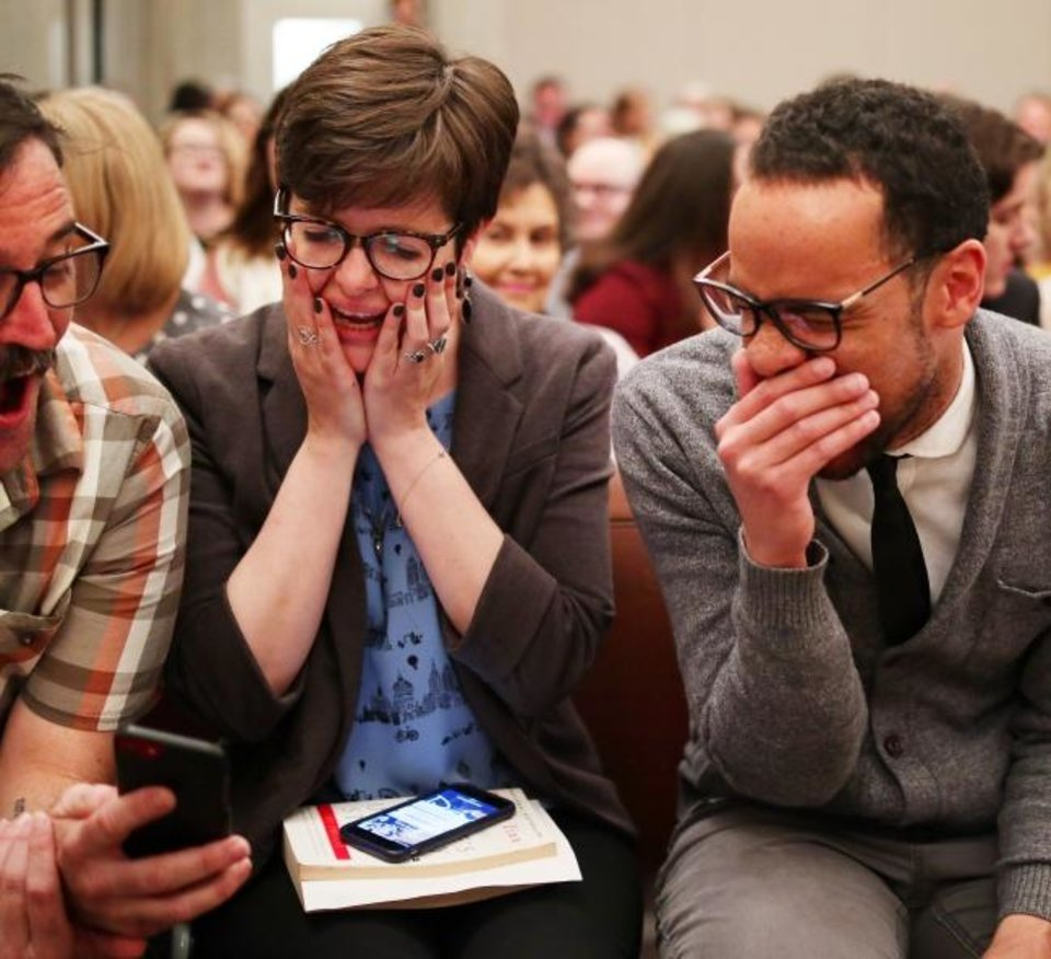 Photo -  JoBeth Hamon and James Cooper react to something on Marty Peercy's phone before their swearing in ceremony Tuesday for the Oklahoma City Council. [Doug Hoke/The Oklahoman]