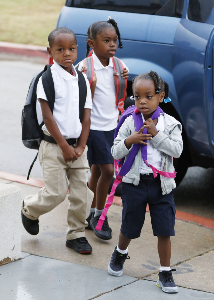 Photo - Four year old Chyna Garcia, front, Zaybion Black, 4, and Serenity Williams, 6, walk up to the front door at the beginning of the first day of school at Thelma Parks Elementary School in Oklahoma City, Okla. Tuesday, Aug. 1, 2017.  Photo by Paul Hellstern, The Oklahoman