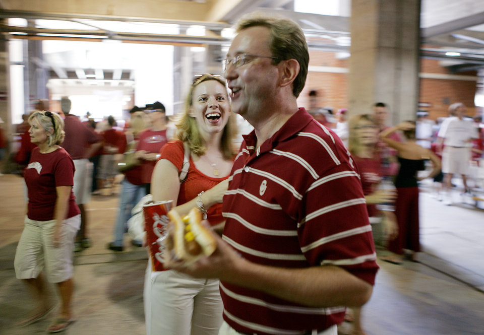 Photo - Oklahoma Sooners fans Whitney and David Hooten smile as they have a pregame hot dog as fans make their way to their seats just before the University of Oklahoma Sooners (OU) college football game against the University of North Texas Mean Green (UNT) at the Gaylord Family - Oklahoma Memorial Stadium, on Saturday, Sept. 1, 2007, in Norman, Okla.
