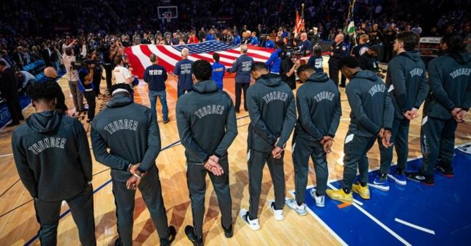 Photo -  Thunder players bow their heads during the playing of the national anthem as first responders from the 1995 Oklahoma City bombing and 2001 terrorist attacks in New York hold the U.S. flag before Friday's game against the Knicks at Madison Square Garden. [ZACH BEEKER/NBAE VIA GETTY IMAGES]