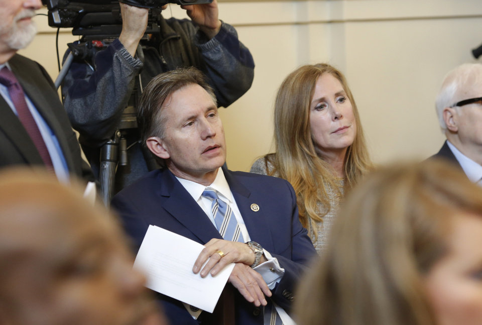 Photo - Mike Hunter and his wife, Cheryl, right, sit in the audience while they wait for his case to be called. Oklahoma Attorney General Mike Hunter can remain on the ballot after the Oklahoma Election Board voted 3-0 on Monday, April 23, 2018, to deny a challenge to his candidacy on residency grounds. Hunter, a Republican, testified he always kept Oklahoma as his permanent home even though he lived in Virginia for years while working in Washington, D.C. for two trade organizations.