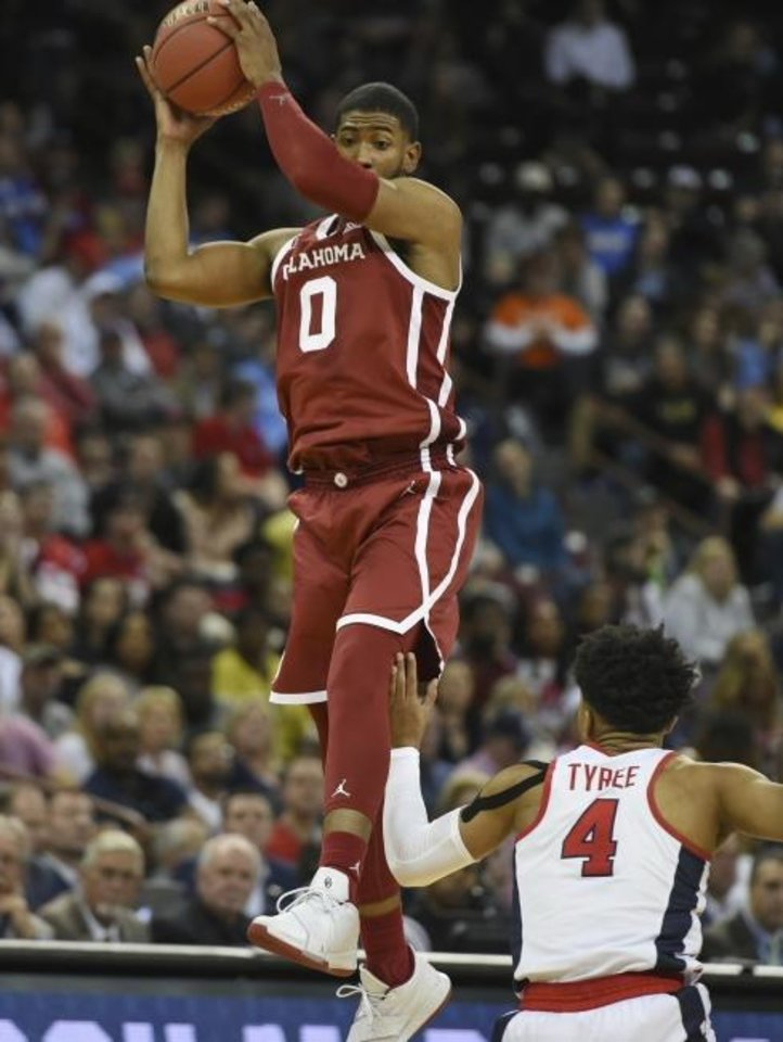 Photo -  OU's Christian James (0) grabs a pass in front of Mississippi's Breein Tyree during the Sooners' 95-72 victory Friday. [AP Photo/Richard Shiro]