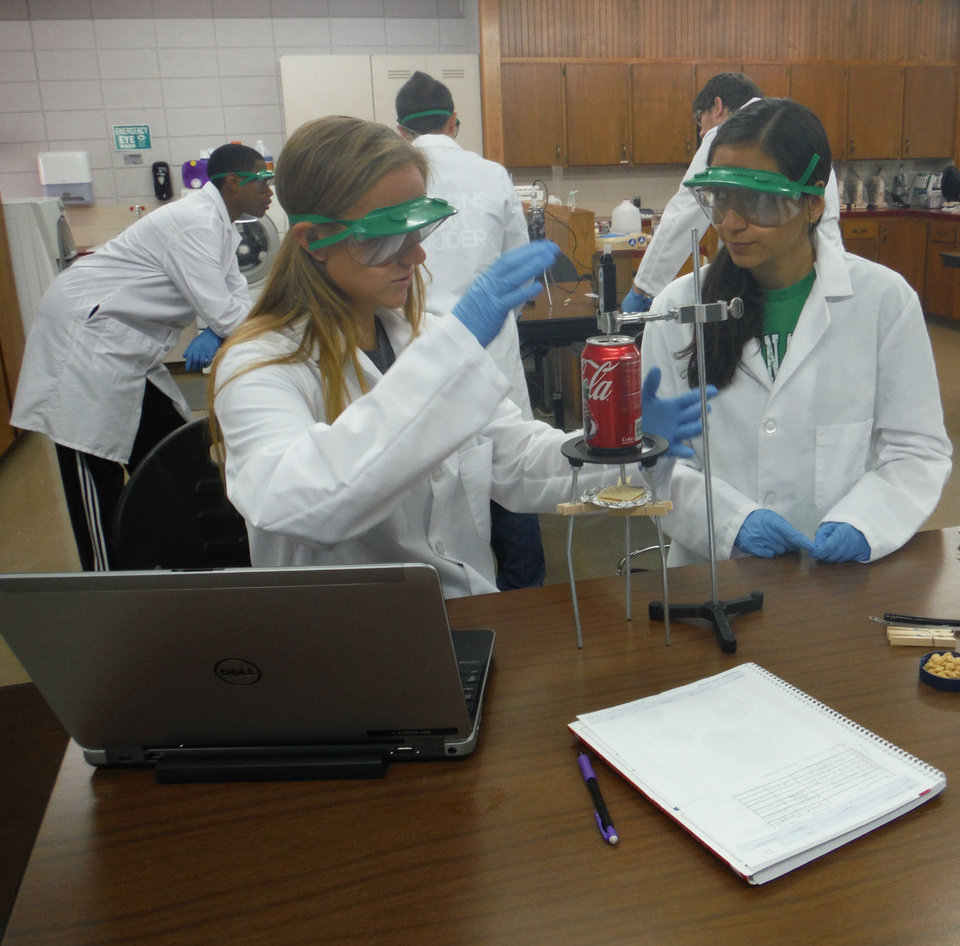 Photo - Natalie Seevers and Alondra Galindo gather information on the calorie counts in food using a calorimeter. (Photo by Thure Tolson)