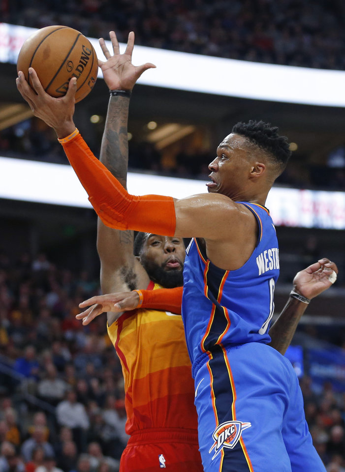 Photo - Oklahoma City Thunder guard Russell Westbrook (0) goes to the basket as Utah Jazz forward Royce O'Neale, left, defends in the first half during an NBA basketball game Monday, March 11, 2019, in Kearns, Utah. (AP Photo/Rick Bowmer)