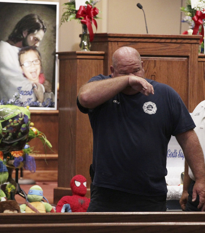 Photo - Townville Fire Chief Billy McAdams wipes tears during a superhero-themed funeral service for Jacob Hall at Oakdale Baptist Church on Wednesday, Oct. 5, 2016, in Townville, S.C. A 14-year-old boy killed his own father, then drove to Townville Elementary and fired on two children and a teacher as recess began. Jacob died Saturday. (Ken Ruinard/The Independent-Mail via AP, Pool)