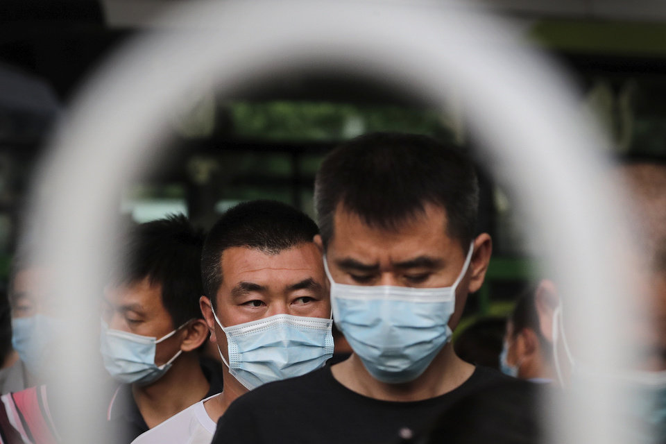 Photo -  Commuters wearing protective face masks to help curb the spread of the new coronavirus line up to board a bus at a bus terminal in Beijing, Monday, June 22, 2020. A Beijing government spokesperson said the city has contained the momentum of a recent coronavirus outbreak that has infected a few hundreds of people, after the number of daily new cases fell to single digits. (AP Photo/Andy Wong)