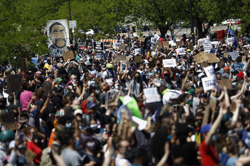 Photo -  FILE - In this May 30, 2020, file photo, people gather for a rally in Minneapolis, following the death of George Floyd. George Soros, the billionaire investor and philanthropist who has long been a target of conspiracy theories, is now being falsely accused of orchestrating and funding the protests over police killings of black people that have roiled the United States. (AP Photo/Julio Cortez)