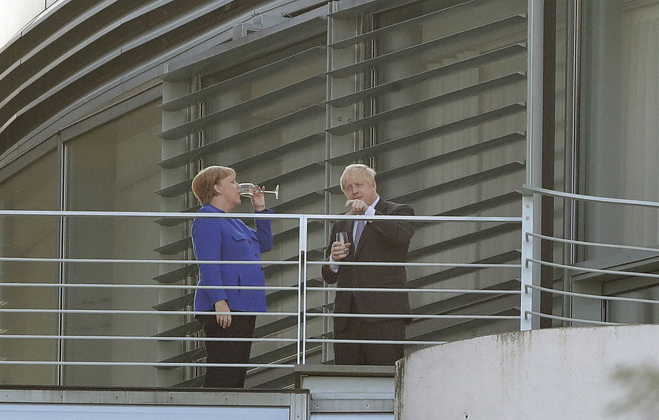 Photo -  German Chancellor Angela Merkel and Britain's Prime Minister Boris Johnson talk as they stand on a balcony prior to a dinner as part of a meeting at the Chancellery in Berlin, Germany, Wednesday, Aug. 21, 2019. (AP Photo/Michael Sohn)