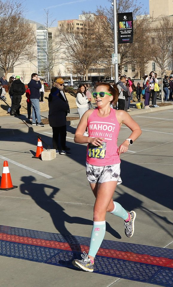 Photo - Andrea McKinney, of Norman, crosses the finish line for Opening Night's inaugural Finale 5K run downtown, Tuesday, December 31, 2019. [Doug Hoke/The Oklahoman Archives]