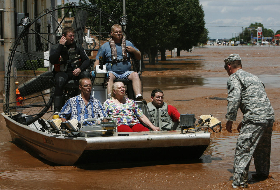 Photo - Kingfisher firefighter Garrick Yost, black suit, Meridian firefighters Terry Waggoner, blue shirt, and John Pross, red shirt, deliver Floyd and Margaret Free, front seat, as a member of the National Guard guides the boat to dry land on Sunday, August 19, 2007, in Kingfisher, Okla. By James Plumlee, The Oklahoman.