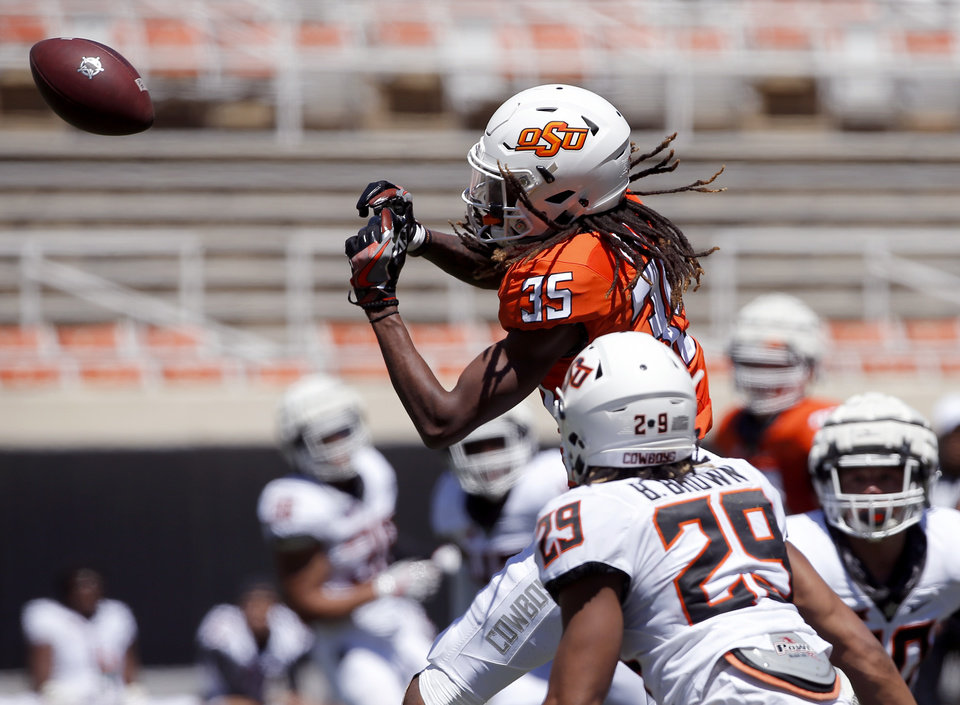 Photo - Oklahoma State's C.J. Moore (35) goes up for a catch as Bryce Brown (29) defends during the Oklahoma State Cowboys spring practice at Boone Pickens Stadium in Stillwater, Okla., Saturday, April 20, 2019.  Photo by Sarah Phipps, The Oklahoman