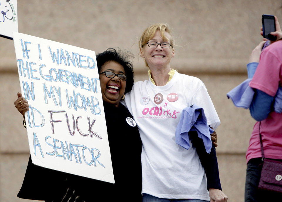 Photo - Warning: The following two photos contain graphic language. Viewer discretion is advised. Sen. Judy Eason McIntyre poses with a protestor during a rally opposing the Personhood measures at the state Capitol, Tuesday, Feb. 28, 2012. Photo by Sarah Phipps, The Oklahoman