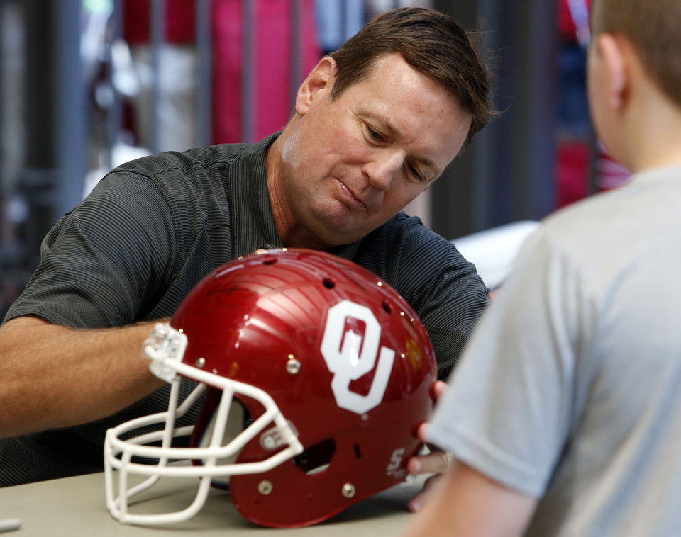 Photo - Bob Stoops signs autographs during Meet the Sooners Day for the University of Oklahoma Sooners (OU) football team at Gaylord Family-Oklahoma Memorial Stadium in Norman, Okla., on Saturday, Aug. 8, 2015. Photo by Steve Sisney, The Oklahoman