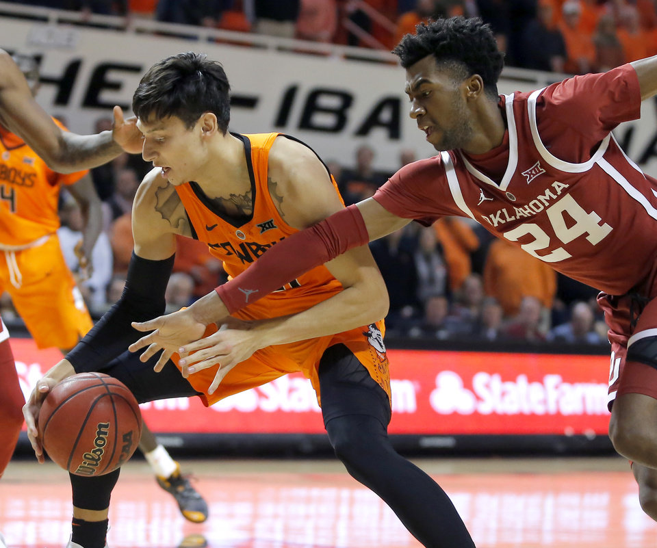 Photo - Oklahoma State's Lindy Waters III (21) goes for the ball beside Oklahoma's Jamal Bieniemy (24) during a Bedlam basketball game between the Oklahoma State Cowboys (OSU) and the University of Oklahoma Sooners (OU) at Gallagher-Iba Arena in Stillwater, Okla., Wednesday, Jan. 23, 2019. Photo by Bryan Terry, The Oklahoman