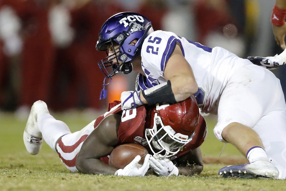Photo - Oklahoma's Rhamondre Stevenson (29) is brought down short of a first down by TCU's Wyatt Harris (25) in the fourth quarter of an NCAA football game between the University of Oklahoma Sooners (OU) and the TCU Horned Frogs at Gaylord Family-Oklahoma Memorial Stadium in Norman, Okla., Saturday, Nov. 23, 2019. Oklahoma won 28-24. [Bryan Terry/The Oklahoman]