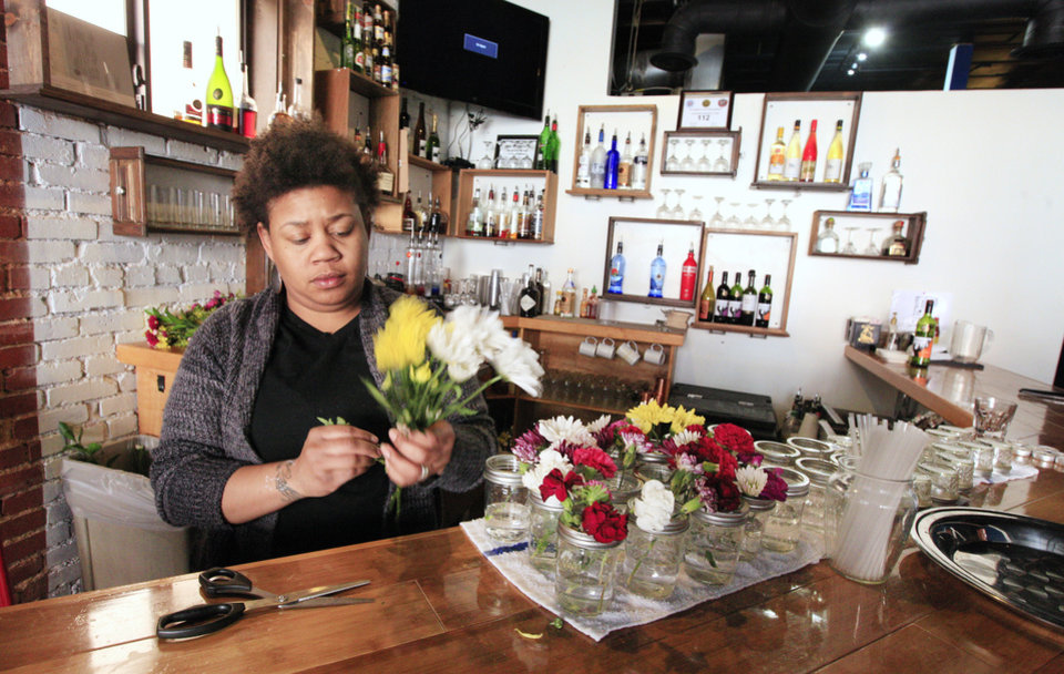 Photo - Owner Chaya Fletcher cuts flowers Wednesday to put on tables inside her Urban Roots restaurant, 322 NE 2 Street, in the Deep Deuce area of Oklahoma City .  Photo by Paul B. Southerland, The Oklahoman  PAUL B. SOUTHERLAND - PAUL B. SOUTHERLAND
