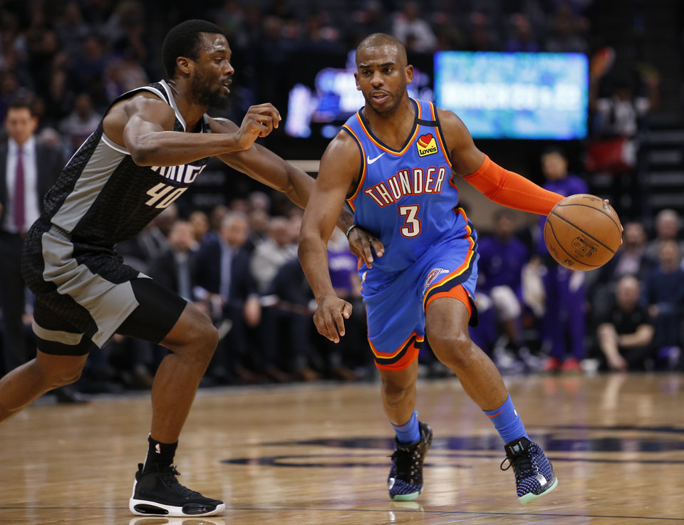 Photo - Oklahoma City Thunder guard Chris Paul, right, drive against Sacramento Kings forward Harrison Barnes, left, during the first quarter of an NBA basketball game in Sacramento, Calif., Wednesday, Jan. 29, 2020. (AP Photo/Rich Pedroncelli)