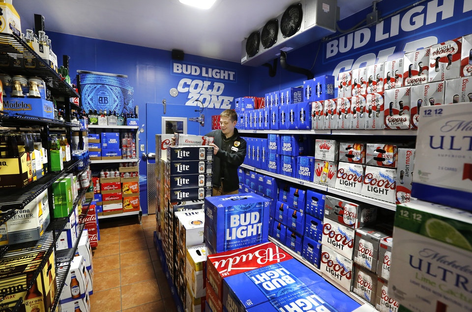 Photo -  Braxtun Brown, an OnCue clerk, arranges beer Oct. 1 inside the Beer Cave, where customers can select chilled brew at their business located at the northwest corner of the E 15th Street and Interstate 35 intersection in Edmond. [JIM BECKEL/THE OKLAHOMAN]