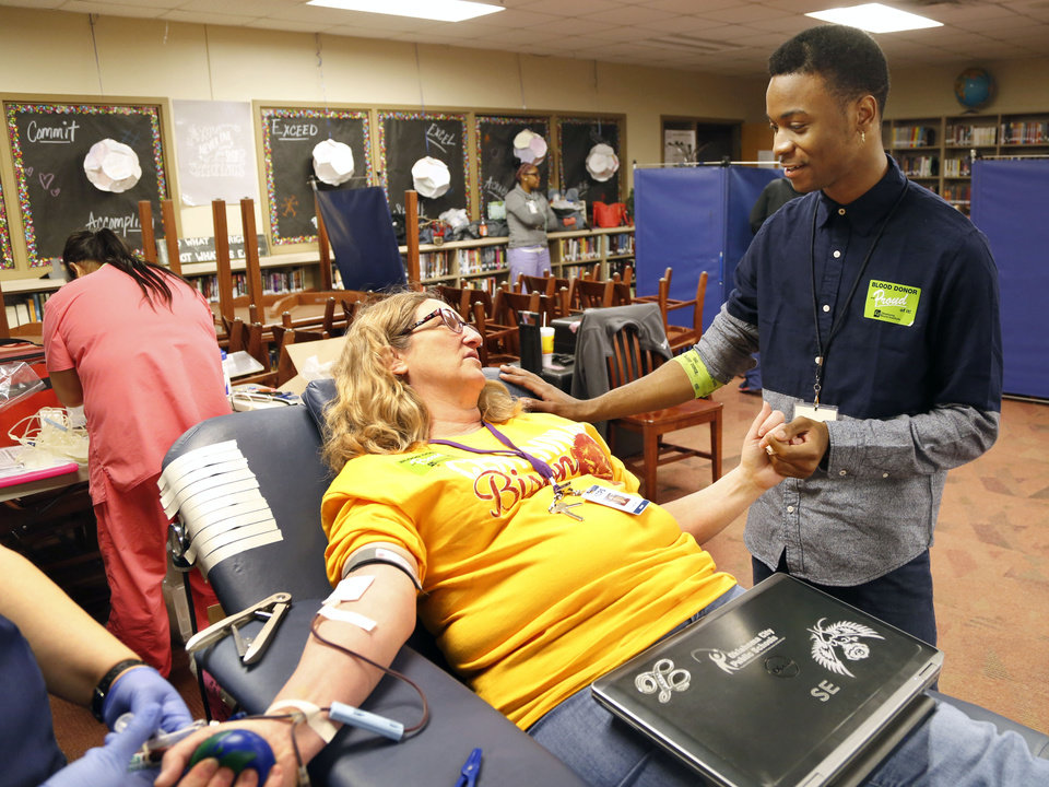 Photo -   Above:  Carlos Jackson, a senior at Oklahoma Centennial Mid-High School and volunteer for the Oklahoma Blood Institute, talks to teacher Laurie Burt during a blood drive he organized at the school.