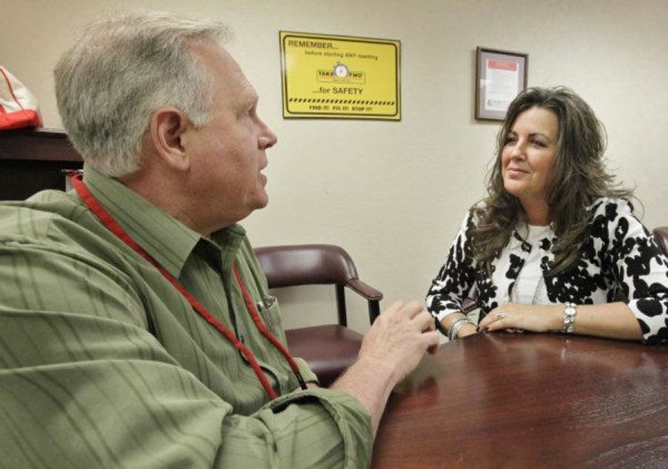 Photo - Julie Young of Marketplace Chaplains  and Buz (cq) Nielsen, a project engineer at G.E. Oil & Gas ESP, talk about his son and daughter-in-law in Iowa. Young helped Nielsen find free marital counseling for the couple. Photo by David McDaniel, The Oklahoman  David McDaniel