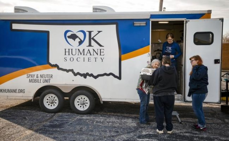 Photo -  Local residents drop off their pets at the Oklahoma Humane Society's mobile veterinary care unit as part of the Best Friends of Pets new