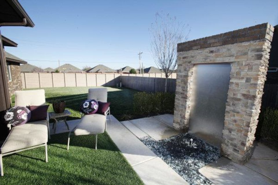 Photo - The patio at the Jeff Click model home features artificial turf and a combo fire-water feature. Photo by Steve Gooch, The Oklahoman  Steve Gooch