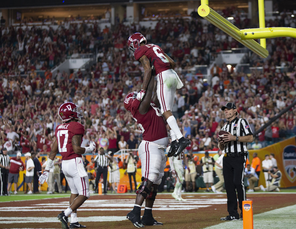 Photo - Alabama Crimson Tide wide receiver DeVonta Smith (6) is lifted into the air by Alabama Crimson Tide offensive lineman Lester Cotton Sr. (66) after a touchdown catch in the fourth quarter in the College Football Playoff semifinals in the Orange Bowl at Hard Rock Stadium in Miami Gardens, Florida on December 29, 2018. [ALLEN EYESTONE/palmbeachpost.com]