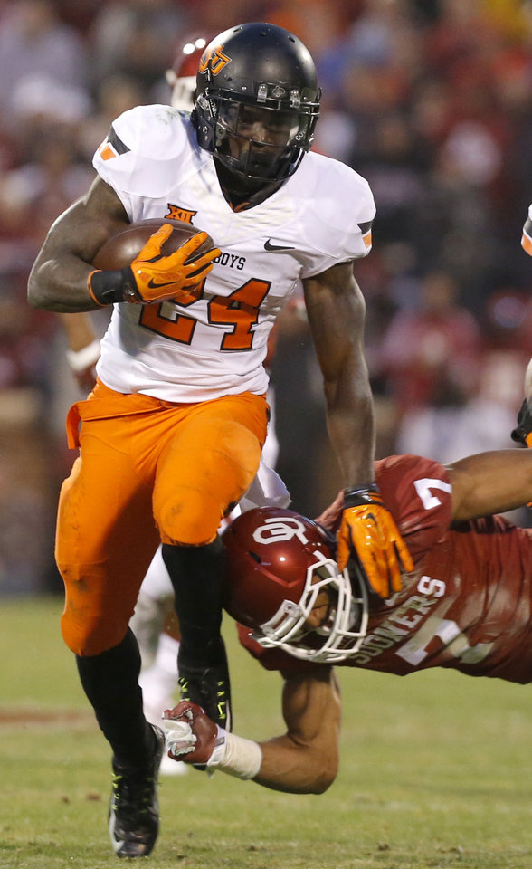 Photo - Oklahoma State's Tyreek Hill (24) tries to get by Oklahoma's Jordan Thomas (7) during the Bedlam college football game between the University of Oklahoma Sooners (OU) and the Oklahoma State Cowboys (OSU) at Gaylord Family-Oklahoma Memorial Stadium in Norman, Okla., Saturday, Dec. 6, 2014. Photo by Sarah Phipps, The Oklahoman