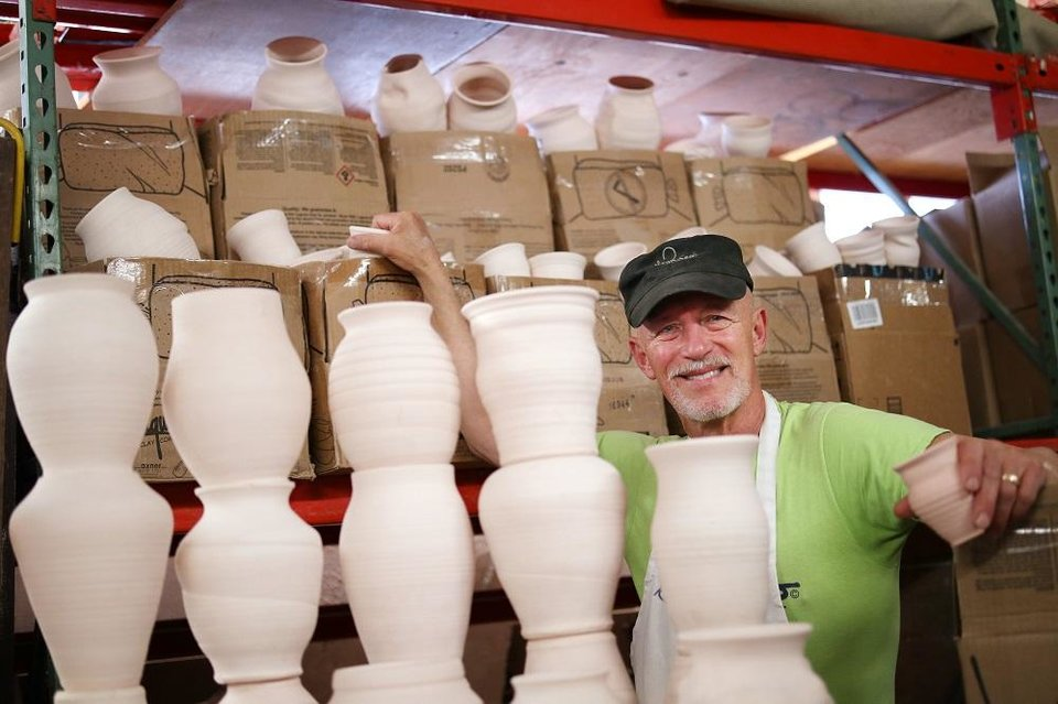 Photo - Collin Rosebrook, owner of Paseo Pottery, poses with pots made for the Pottery Place booth at the Festival of the Arts, which are now being stored because of the cancellation of the festival due to the COVID-19 pandemic, Monday, April 20, 2020. [Doug Hoke/The Oklahoman]