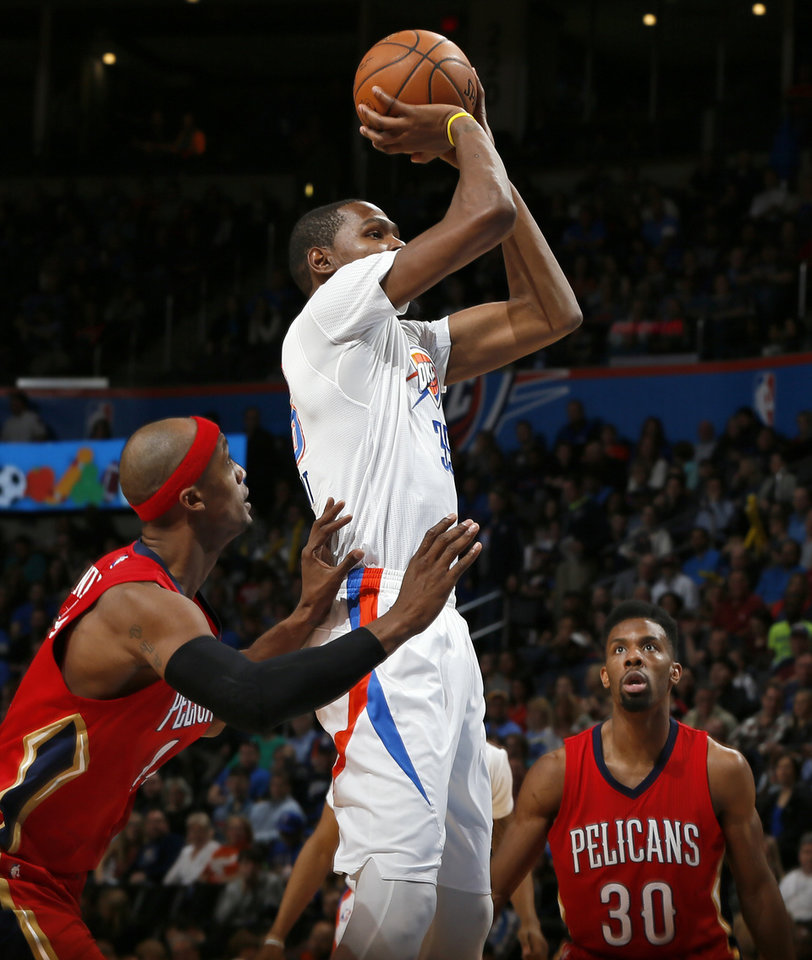 Photo - Oklahoma City's Kevin Durant (35) shoots between New Orleans' Dante Cunningham (44), left, and Norris Cole (30) during an NBA basketball game between the New Orleans Pelicans and the Oklahoma City Thunder at Chesapeake Energy Arena in Oklahoma City, Thursday, Feb. 11, 2016.  Photo by Nate Billings, The Oklahoman