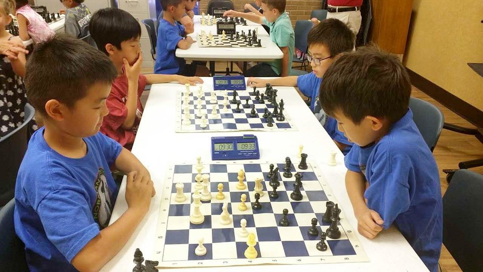 Photo -  Norman Chess Club players who took part in the tournament included, front table from left, Ryan Chen and Daniel Wang. At rear table are Patrick Nguyen and Andrew Wang. [Photo provided]