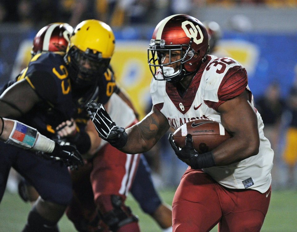 Photo - Oklahoma's Samaje Perine (32) reaches to stiff-arm a West Virginia defender during the fourth quarter of an NCAA college football game in Morgantown, W.Va., Saturday, Sept. 20, 2014. (AP Photo/Tyler Evert)