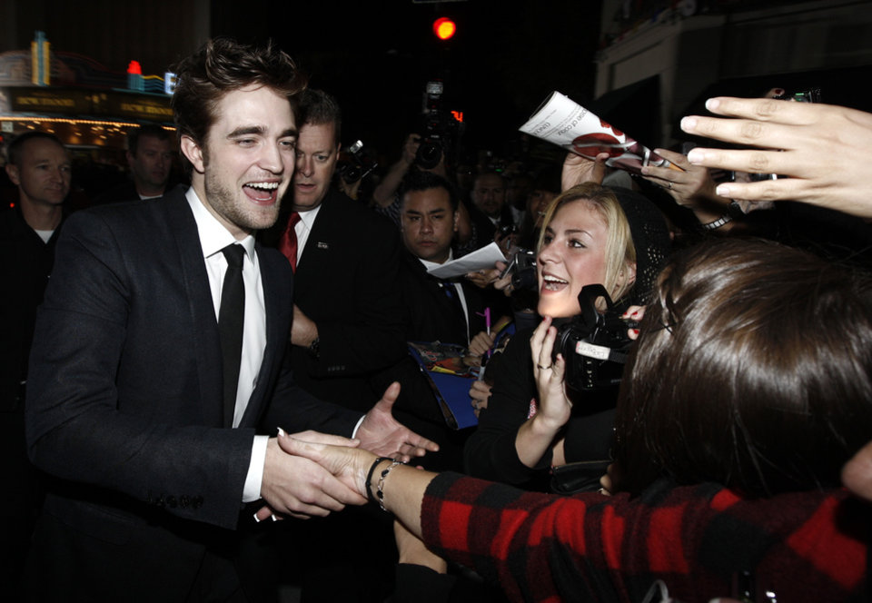 Photo - Actor Robert Pattinson signs autographs as he arrives at The Twilight Saga: New Moon premiere in Westwood, Calif. Monday, Nov. 16, 2009.  (AP Photo/Matt Sayles) ORG XMIT: CAGS138