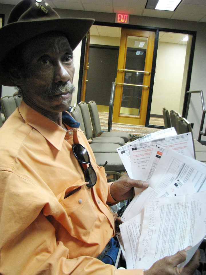 Photo - Syvertic King, 60, waits at the Embassy Suites Hotel in Oklahoma City. Nearly 200 black farmers from the area gathered at the hotel Friday, April 13, for assistance in filling out claim forms to see if they qualify for compensation from a $1.2 billion lawsuit. The lawsuit was filed on the grounds that tens of thousands of black farmers had been discriminated against by the USDA in the 1980s and 1990s and were denied loans and grants. King holds the more than 30 pages of paperwork needed to file a claim. Oklahoman  Vallery Brown - THE OKLAHOMAN