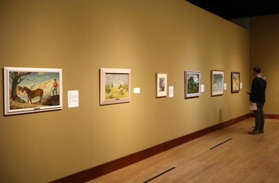 Photo -  A visitor looks at landscapes on view in the Oklahoma City Museum of Art exhibit