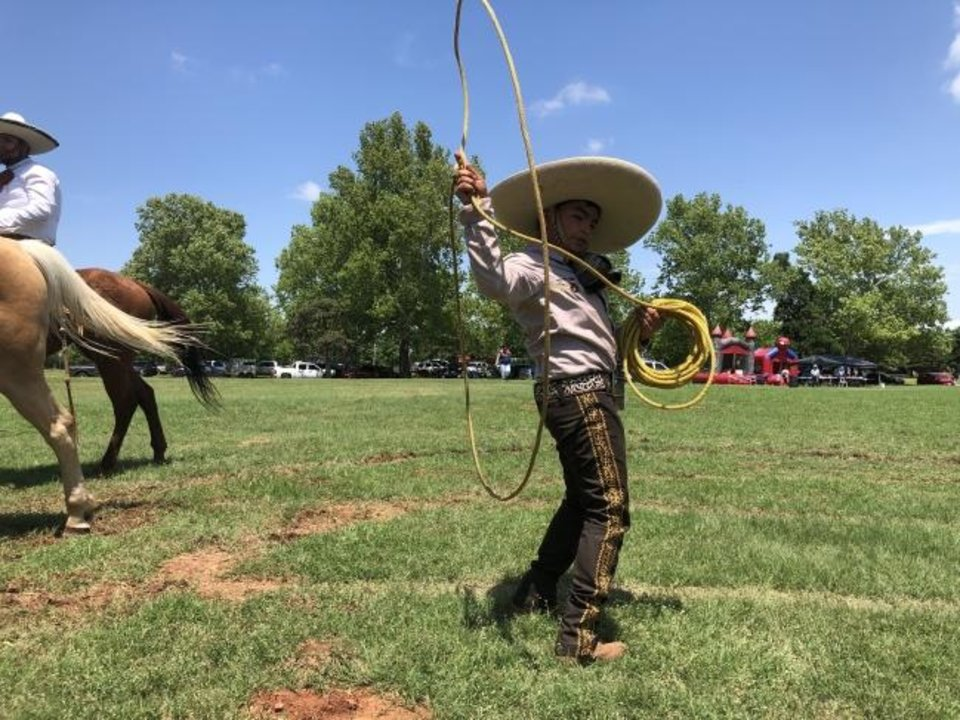 Photo -  Christian Perez, 10, of Oklahoma City, shows off his trick-roping skills Sunday at the Cinco de Mayo festival in south Oklahoma City. [ROBERT MEDLEY/THE OKLAHOMAN]