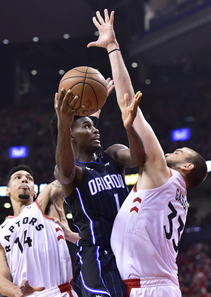 Photo -  Orlando Magic forward Jonathan Isaac (1) jumps towards the basket between Toronto Raptors guard Danny Green (14) and Toronto Raptors center Marc Gasol (33) during the second half in Game 5 of a first-round NBA basketball playoff series, Tuesday, April 23, 2019 in Toronto. (Frank Gunn/Canadian Press via AP)