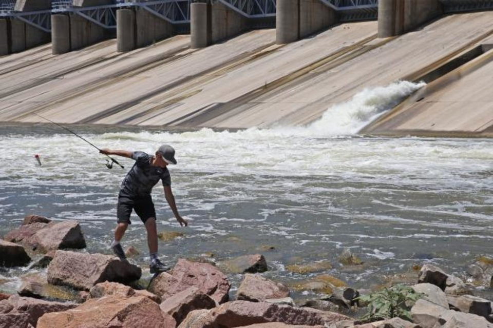 Photo -  Tate Tipton, age 14, of Cross Plains, Texas, walks across the rocks while fishing below the dam at Canton Lake.
