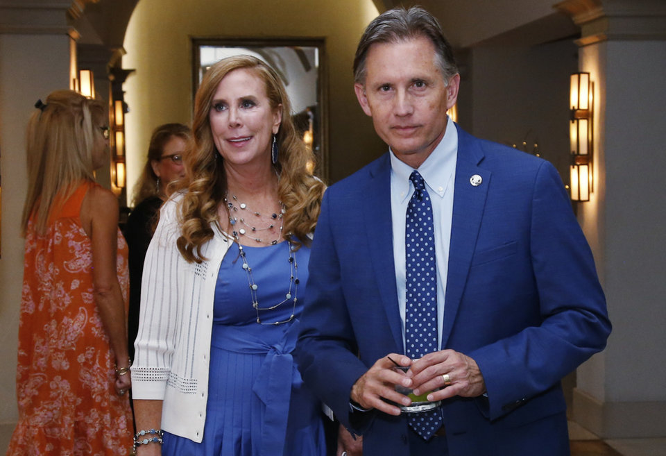 Photo - Mike Hunter, running in the Republican primary runoff for Attorney General, walks through a watch party with his wife, Cheryl, left, in Oklahoma City, Tuesday, Aug. 28, 2018. (AP Photo/Sue Ogrocki)