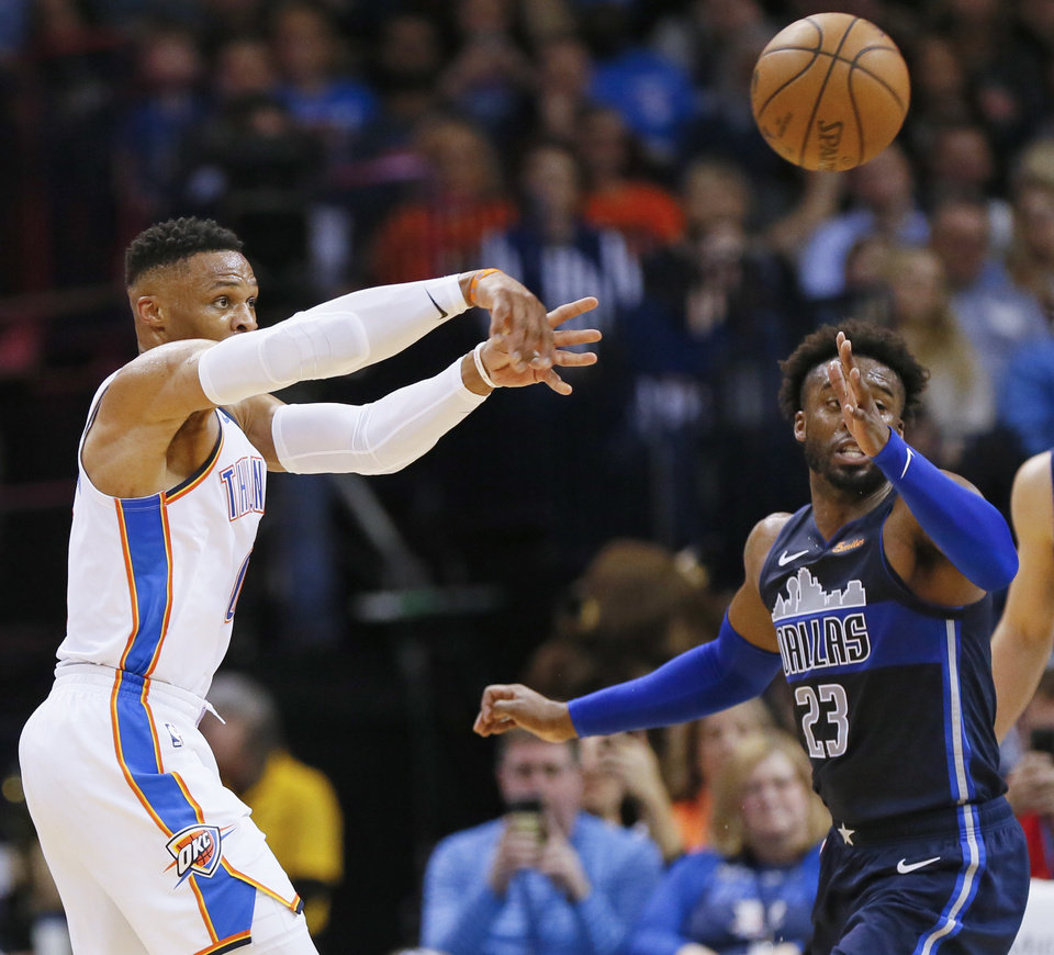 Photo - Oklahoma City's Russell Westbrook (0) passes away from Dallas' Wesley Matthews (23) during an NBA basketball game between the Oklahoma City Thunder and Dallas Mavericks at Chesapeake Energy Arena in Oklahoma City, Monday, Dec. 31, 2018. Oklahoma City won 122-102. Photo by Nate Billings, The Oklahoman