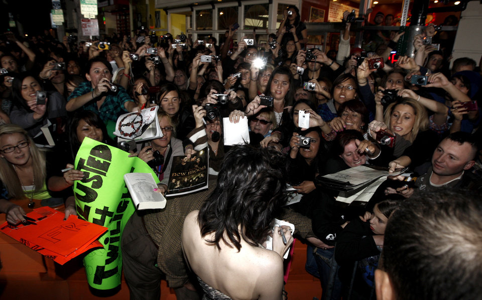Photo - Actress Kristen Stewart signs autographs as she arrives at The Twilight Saga: New Moon premiere in Westwood, Calif. Monday, Nov. 16, 2009.  (AP Photo/Matt Sayles) ORG XMIT: CAGS144