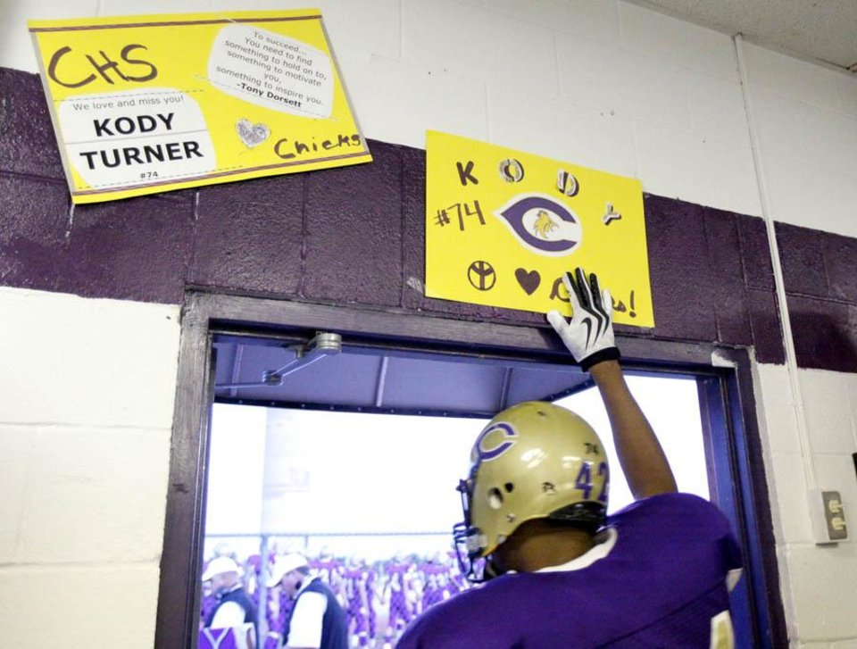 Photo -  TJ Filer touches a poster honoring Kody Turner before running onto the field at the football game between Chickasha and Capitol Hill at Chickasha High School, Friday, Oct. 1, 2010, at the Bethany, Okla.  It was the first home game since the death of player Kody Turner. Photo by Sarah Phipps, The Oklahoman