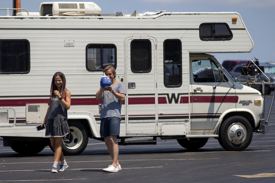 Photo -  Tammin Sursok and Tom Felton stand outside an RV between takes as they film a scene on the set of