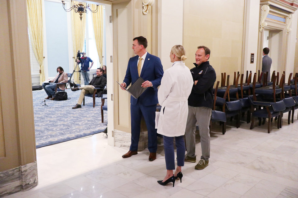 Photo - Gov. Kevin Stitt, Kayse Shrum and Jerome Loughridge wait outside of the Blue Room before the media briefing for the Governor's Solution Task Force to provide an update on Oklahoma's COVID-19 response in the Blue Room of the Capitol Wednesday, April 15, 2020.  [Photo by Doug Hoke/The Oklahoman]