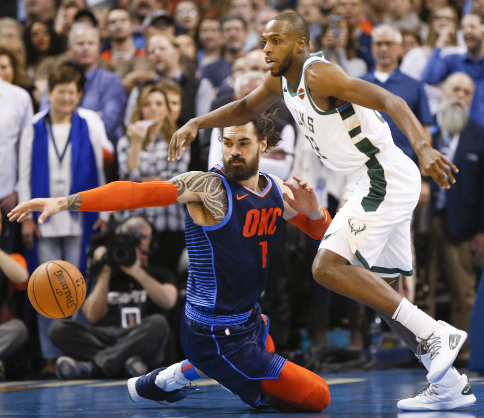 Photo - Oklahoma City's Steven Adams (12) and Khris Middleton (22) chase the ball during an NBA basketball game between the Milwaukee Bucks and the Oklahoma City Thunder at Chesapeake Energy Arena in Oklahoma City, Sunday, Jan. 27, 2019. Photo by Nate Billings, The Oklahoman